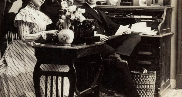 Ảnh chụp năm 1899, trong hình là một nữ nhân viên đánh máy. Dưới thời nữ hoàng Victoria, phụ nữ Anh đã bắt đầu được làm tại các văn phòng. Vào thời điểm này phụ nữ vẫn chuộng diện các loại váy dày và còn khung váy khi đi làm. Tuy nhiên đến gần cuối thế kỷ 19, những chiếc váy như thế trở nên lỗi mốt.