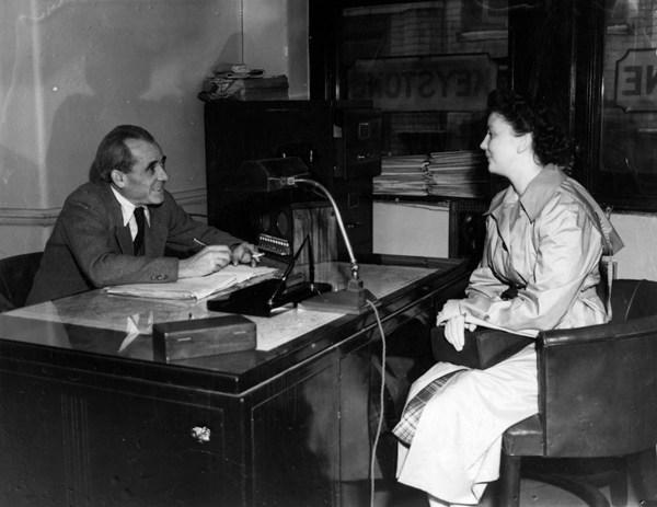 Người phụ nữ ngày đến phỏng vấn cho một công việc tại văn phòng nhiếp ảnh Keystone vào ngày 28/5/1950. Người phỏng vấn cô mặc vest và đeo cà vạt trong khi cầm một điếu thuốc. Cô vẫn mặc áo khoác bên ngoài, bên trong là váy kẻ sọc. Tóc cô được búi cẩn thận.