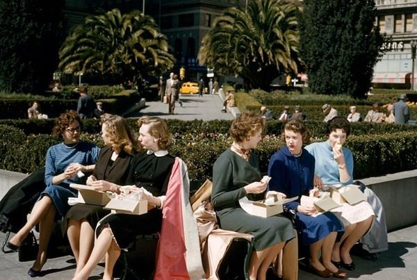 Các nữ nhân viên văn phòng ăn trưa tại Union Square, San Francisco, California vào năm 1956. Bức ảnh màu tuyệt đẹp này cho thấy rõ nét sự đa dạng trong phong cách thời trang công sở . Các cô mặc trang phục nhiều màu sắc (dù đa số các màu tông xanh), được thiệt kế nhiều kiểu dáng từ cổ tim, cổ huyền cổ V-line, đến thời trang tóc đa dạng.
