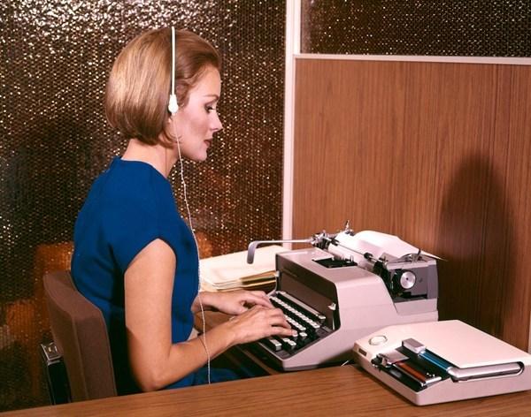 Một nữ văn thư đang sử dụng tai nghe băng ghi âm để gõ lại tại Mỹ năm 1960.