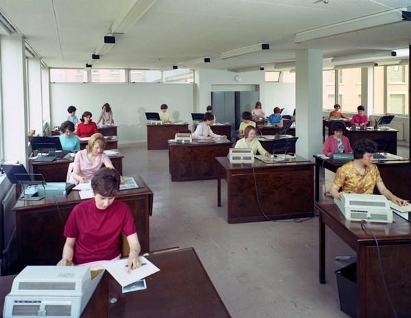 Ảnh chụp tại văn phòng điều hành tại Huntsman House, trụ sở chính của hãng bia Tetley tại Leeds, West Yorkshire năm 1968. Các văn thư đang sử dụng máy Sumlock, tiền thân của máy tính. Họ mặc quần áo với các màu sắc tươi sáng. Những người phụ nữ có một loạt các kiểu tóc được tạo hình nhờ keo xịt tóc.