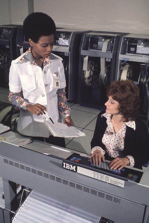 Hai phụ nữ làm việc với một máy tính IBM 1130 năm 1974. Cả hai mặc áo có cổ rộng và mái tóc để kiểu tự nhiên.