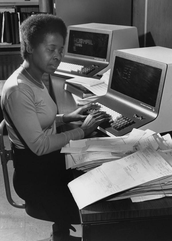 Năm 1980, một nhân viên văn phòng nhập dữ liệu vào một máy tính tại một công ty trực ở Boston, Massachusetts. Có thể thấy cô mặc trang phục đơn giản thoải mái hơn rất nhiều.