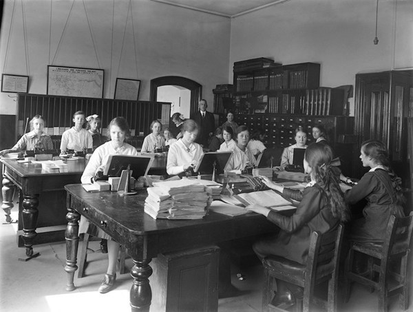 Khi Thế chiến thứ nhất được diễn ra, phụ nữ tham gia nhiều hơn vào các công việc ở hậu phương. Trong hình là một văn phòng đường sắt tại Horwich, Lancashire, Anh năm 1917. Các nữ nhân viên văn phòng giai đoạn này cũng ưa chuộng áo blouse trắng cùng váy dài, nhưng để phù hợp với công việc, áo đã được may ôm sát người hơn.