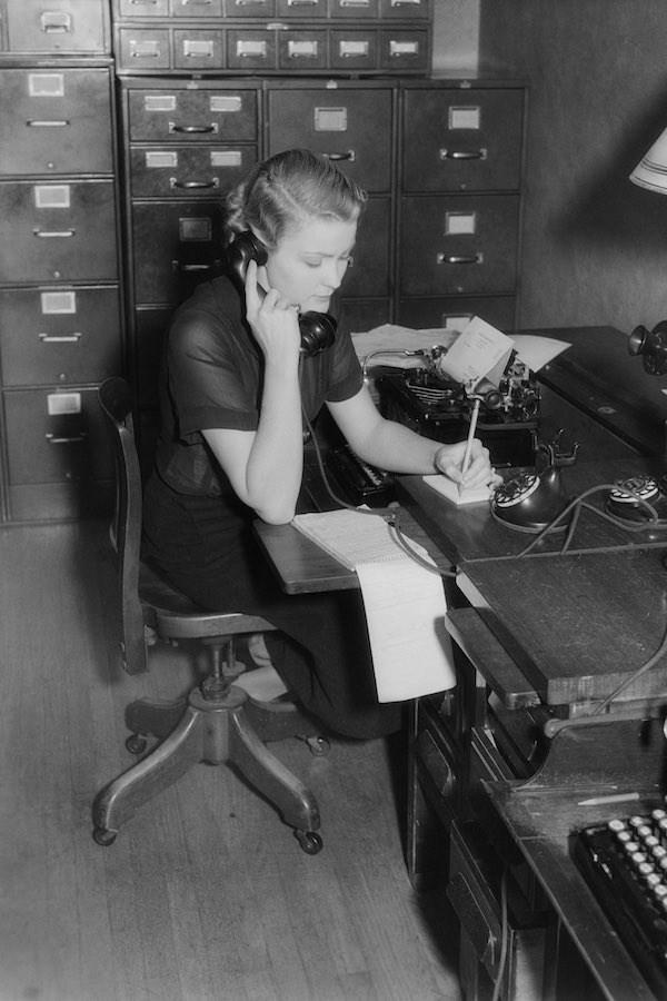 Trong ảnh là một nữ thư ký người Mỹ được chụp vào năm 1930. Trang phục cô khác hẳn các nữ nhân viên văn phòng tại Anh, cô diện áo ngắn tay, váy màu đen ôm gọn với kiểu tóc bob ngắn và uốn lọn to. Trông cô vừa sành điệu vừa phóng khoáng hơn các trang phục kín đáo của phụ nữ Anh.