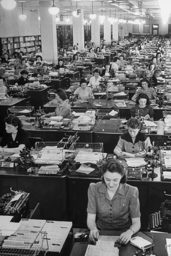 """Các cô gái làm công việc xử lý các đơn hàng tại công ty sách """"Book of the Month Club"""" năm 1942 tại Mỹ. Những người phụ nữ mặc nhiều áo cánh và váy, hoạ tiết trang trí đa dạng, hầu hết có V-cổ. Đa số các cô để tóc dài nhưng được buộc gọn gàng bằng trâm hoặc lưới."""