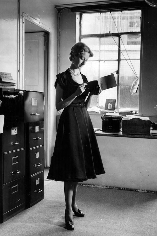 """Bức ảnh chụp vào 19/8/1950 được xuất bản trong """"Picture Post"""" với chú thích """" Một phụ nữ mặc chiếc váy satin màu đen của Brenner với ren con xung quanh tay áo, cổ và các đường viền không thực sự phù hợp để mặc đi làm."""""""